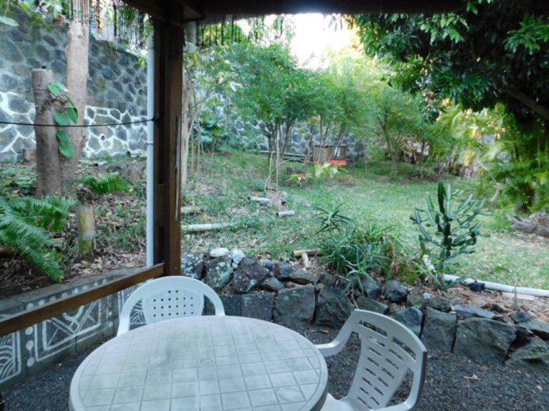 Vue sur le jardin de la terrasse du Bungalow papaye en location meublée
